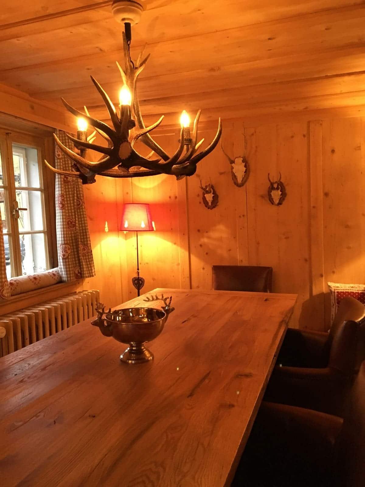 Alpenchic Projekt Klosters mit Altholztisch aus Eiche, Kronleuchter aus Hirschgeweih und schönem Vintage Lederstuhl